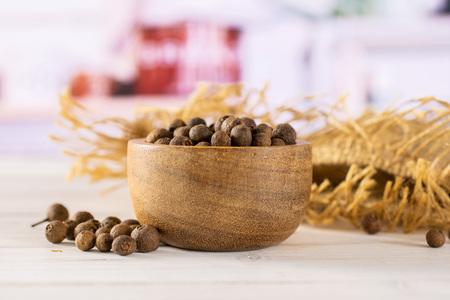 Lot of whole dry brown allspice berries with wooden bowl on jute cloth with grey kitchen in background Standard-Bild - 119677984