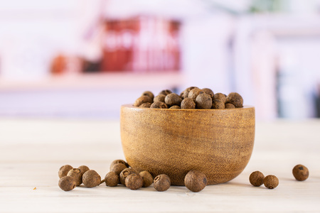 Lot of whole dry brown allspice berries with wooden bowl with grey kitchen in background Standard-Bild - 119677936