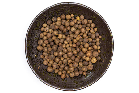 Lot of whole dry brown allspice berries in a grey ceramic bowl flatlay isolated on white background Stock Photo