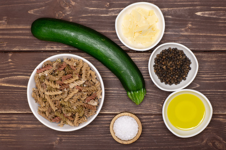Ingredients. recipe step by step fusilli pasta with zucchini flatlay on brown wood