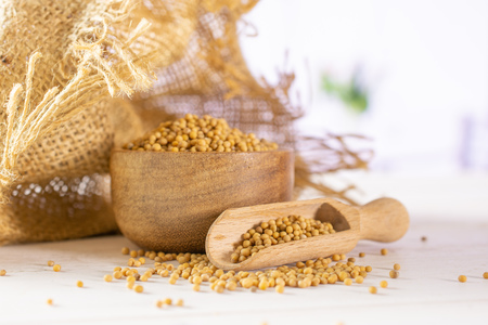 Lot of whole white mustard seeds with wooden bowl , wooden scoop in a jute bag with red flowers in a white kitchen