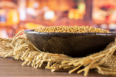 Lot of whole white mustard seeds on grey ceramic plate on jute cloth in a rustic kitchen