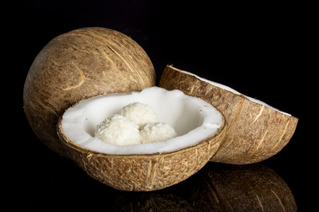 Group of one whole two halves of fresh bio coconut with three small cocoa balls isolated on black glass