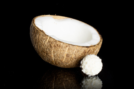 One half of fresh bio coconut with a small cocoa ball isolated on black glass