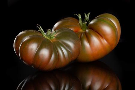 Group of two whole fresh tomato primora isolated on black glass Stock Photo