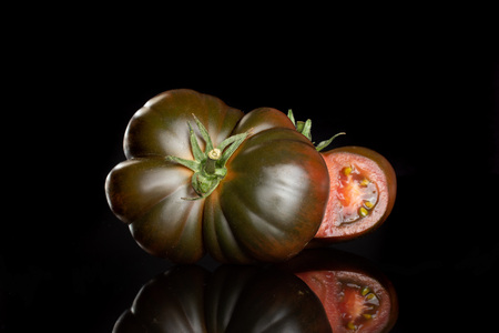 Group of one whole one half of meaty fresh tomato primora isolated on black glass Stock Photo