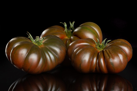 Group of three whole fresh tomato primora isolated on black glass