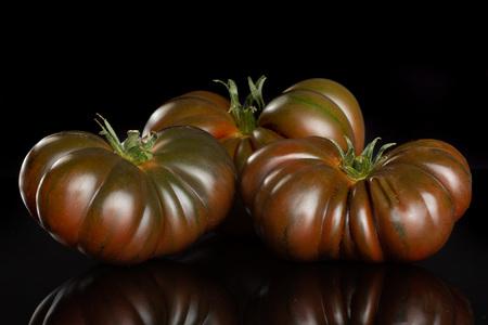 Group of three whole fresh tomato primora isolated on black glass Stock Photo
