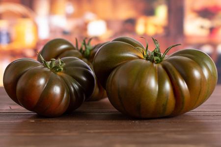 Group of three whole fresh tomato primora in a rustic kitchen