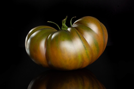One whole fresh tomato primora isolated on black glass