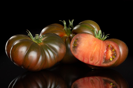 Group of two whole one half of fresh tomato primora isolated on black glass
