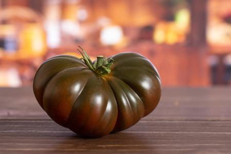 One whole fresh tomato primora in a rustic kitchen