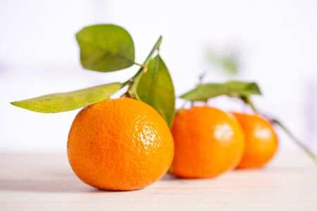 Group of three whole fresh orange mandarine one by one with green leaves in a white kitchen