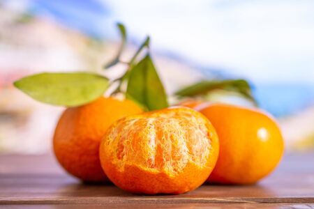 Group of three whole fresh orange mandarine with green leaves one fruit is half peeled with italian mountains in background