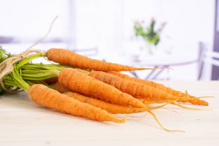 Lot of whole fresh orange carrot bunch with greens tied by jute with red flowers on white in background Stock Photo