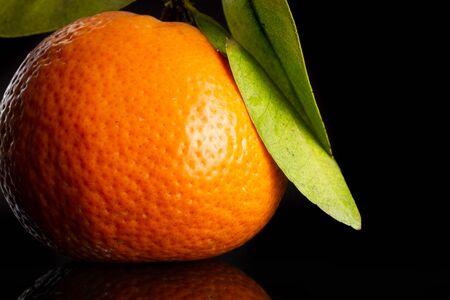 Macro closeup of one whole fresh orange mandarine with green leaves isolated on black glass Imagens