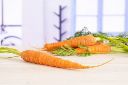 One whole fresh orange carrot in focus with greens with blue window in a white kitchen