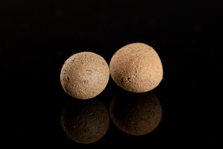 Group of two whole brown clay pebbles (leca) isolated on black glass Stockfoto