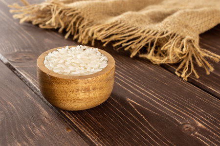 Lot of whole white jasmine rice grains in a wooden bowl on jute cloth on brown wood