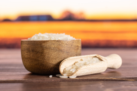 Lot of whole white jasmine rice grains in a wooden bowl with wooden scoop with autumn field in background