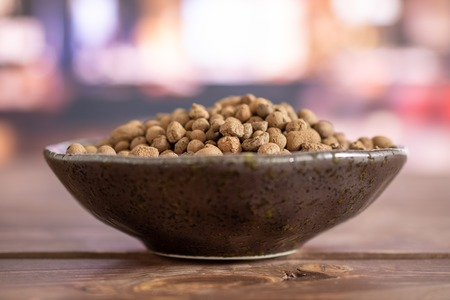 Lot of whole brown clay pebbles (leca) on grey ceramic plate in a restaurant
