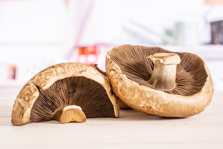 Group of one whole one half of fresh brown mushroom portobello in a white kitchen Stock Photo