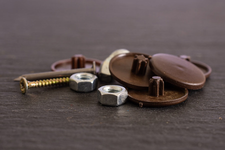 Lot of whole plast plugs, metal nails and nuts work item on grey stone Reklamní fotografie