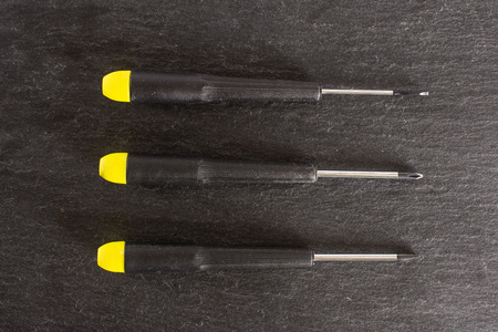Group of three whole screwdrivers with a yellow black plastic handle work item flatlay on grey stone