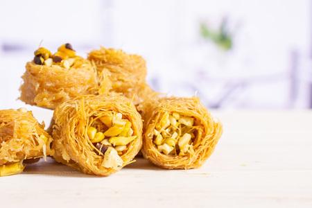 Closeup of seven whole sweet lebanese baklava piece bird nest variety in a white kitchen