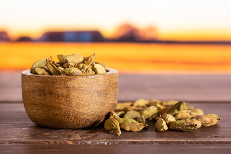 Lot of whole true cardamom pod near and in a wooden bowl with autumn field in background