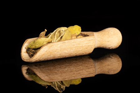 Lot of whole true cardamom pods in a wooden scoop isolated on black glass