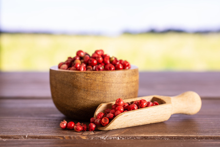 Lot of whole peruvian pink pepper in a wooden bowl with wooden scoop with green wheat field