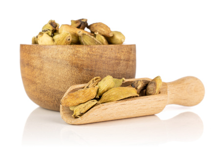 Lot of whole true cardamom pod in a wooden bowl with wooden scoop isolated on white background