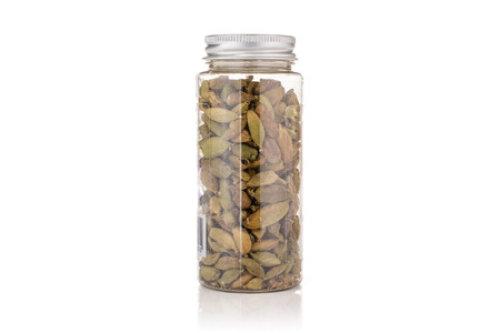 Lot of whole true cardamom pod in a plastic bottle isolated on white background