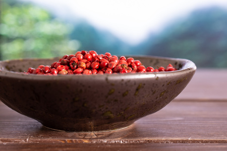 Lot of whole peruvian pink pepper on grey ceramic plate in a foggy jungle mountains