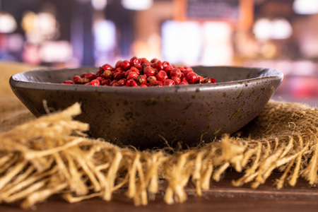 Lot of whole peruvian pink pepper on grey ceramic plate on jute cloth in a restaurant