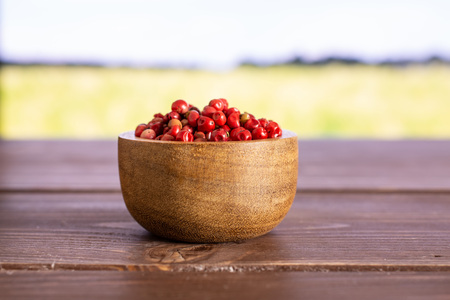 Lot of whole peruvian pink pepper in a wooden bowl with green wheat field 免版税图像