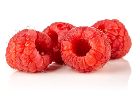 Group of four whole fresh red raspberry isolated on white