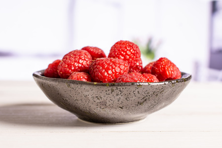 Lot of whole fresh red raspberry on grey ceramic plate in a white kitchen Фото со стока