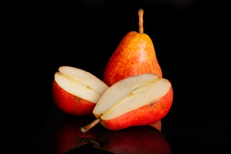 Group of one whole two halves of juicy fresh red pear isolated on black glass