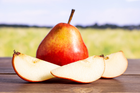 Group of one whole three slices of fresh red pear with green wheat field