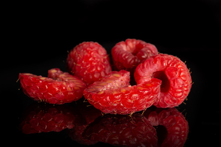 Group of three whole two halves of fresh red raspberry isolated on black glass Фото со стока