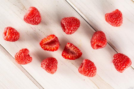 Group of lot of whole two halves of fresh red raspberry flatlay on white wood Фото со стока