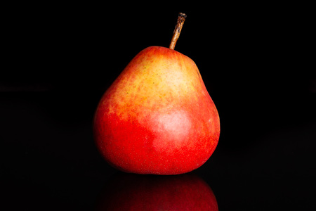 One whole juicy fresh red pear isolated on black glass Фото со стока