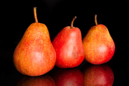 Group of three whole fresh red pear in row isolated on black glass
