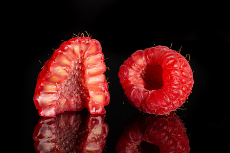 Group of one whole one half of fresh red raspberry cross section isolated on black glass