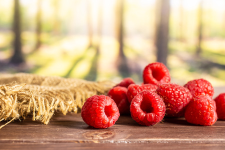 Lot of whole fresh red raspberry on jute cloth in a forest