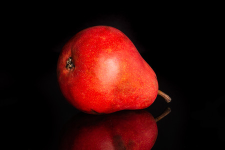 One whole ripe fresh red pear isolated on black glass