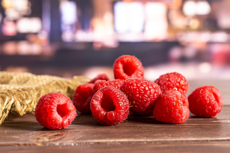 Lot of whole fresh red raspberry on jute cloth in a restaurant Фото со стока