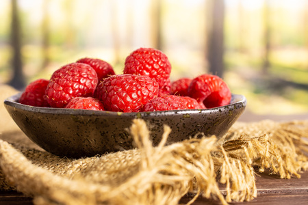 Lot of whole fresh red raspberry on grey ceramic plate on jute cloth in a forest